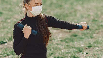 Woman wearing mask outside during Covid lockdown doing daily exercise with barbells